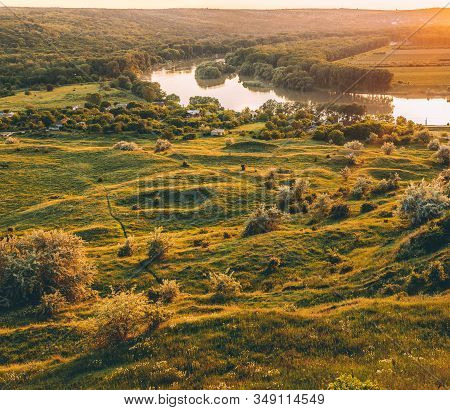 Tranquil Peaceful Summer Landscape With Calm River Flowing Among Green Hilly Field In Sunny Day