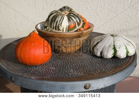 Three kinds of pumpkins on a table with a wooden sandal bowl- Food and decoration as well.. There are more than  800 sorts, but not all are eatable