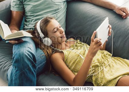Father and pre teen daughter playing tablet and reading book while relaxing together on couch in room at home. Good parent and child relations.