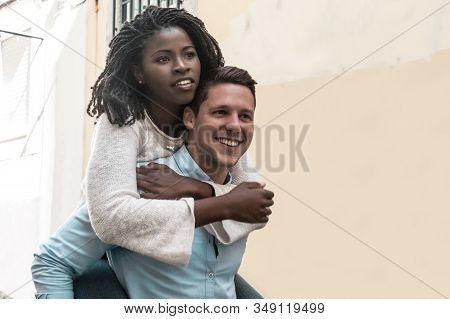 Guy Carrying Black Girlfriend On Back In City. Happy Interracial Couple In Street. Romance And Happi