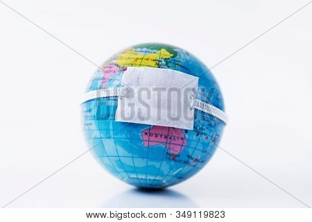 closeup of a terrestrial globe with a protective mask placed over China, depicting the recent coronavirus outbreak or the protection against the air pollution
