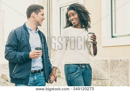 Happy Cheerful Interracial Couple Enjoying Date. Afro American Girl And Her Caucasian Boyfriend Hold