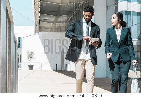 Business People Talking And Walking Along Street. Business Man And Woman Wearing Formal Clothes And
