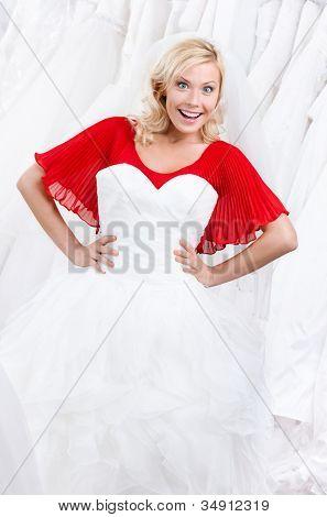 Bride admires her wedding dress, white background