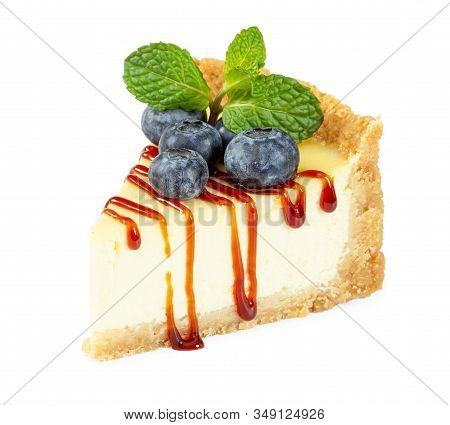 Cheesecake With Fresh Blueberries, Caramel Syrup And Mint Leaves Isolated On White Background.