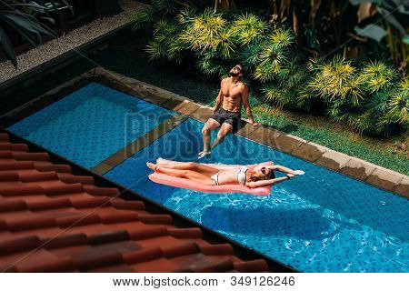 Couple Relaxing By The Pool. Couple Outside Relaxing In Swimming Pool In The Summertime. Man And Wom