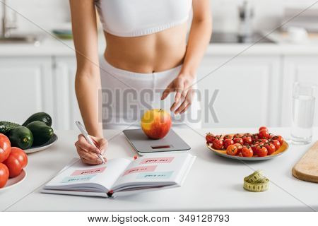 Cropped View Of Fit Sportswoman Writing Calories While Weighing Apple On Kitchen Table, Calorie Coun