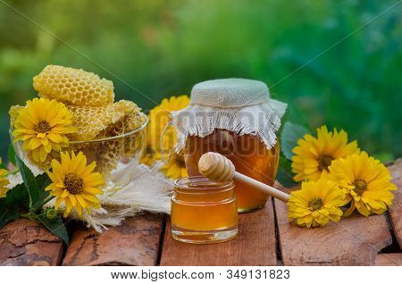 Honey Jar And Wooden Stick On Table Against Green Background