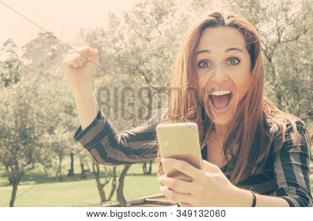 Overjoyed Crazy Lady With Mobile Phone Getting Great News. Happy Woman Holding Smartphone, Raising F