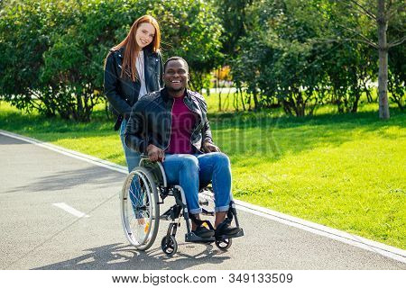 Afro American Man Sitting On Wheelchair , His Redhaired Ginger Girlfriend Rolling Stroller In Autumn