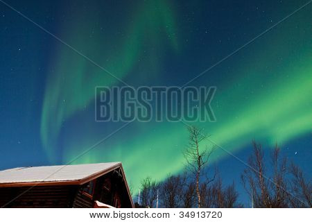 Northern lights (Aurora borealis) above cabins