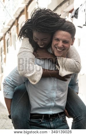 Young Man Laughing And Carrying Woman On Back Outdoors. Happy Interracial Couple In Street. Romance
