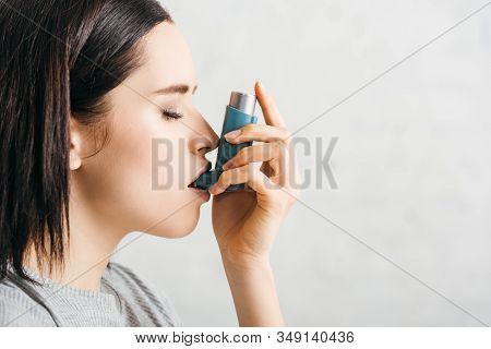 Side View Of Attractive Girl Using Asthmatic Inhaler On White Background