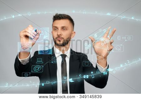 Front View Of Concentrated Businessman In Suit Working With Digital Tactile Charts Screen Using Fing