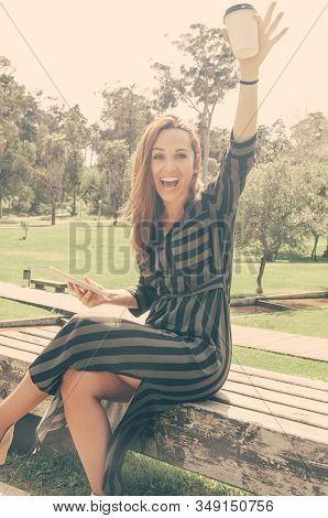 Happy Overjoyed Lady Celebrating Great News Or Success. Woman Sitting On Park Bench, Holding Tablet,