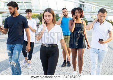 Front View Of Friends Using Smartphones While Walking On Street. Cheerful Young People Strolling On