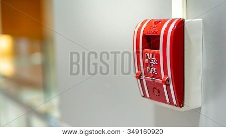 Red Fire Alarm Switch On Concrete Wall In Office Building. Industrial Fire Warning System Equipment