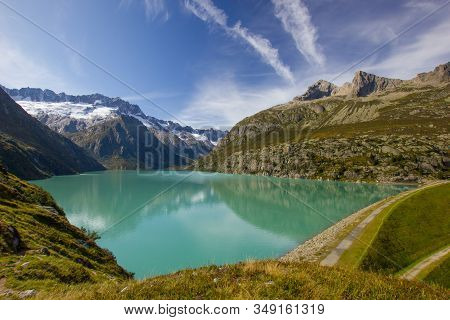Lake Goeschenen In The Swiss Mountains With The Dam On The Rigth Side