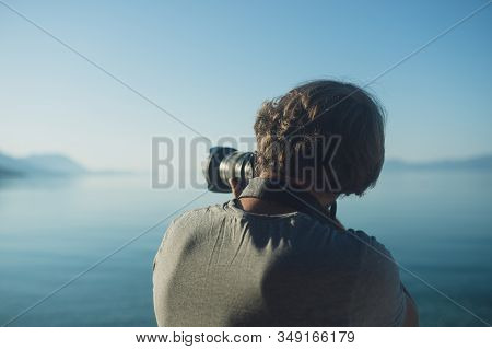 View From Behind Of A Young Male Professional Photographer Taking A Photo Of A Distant Island As He