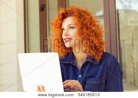 Attractive Thoughtful Daydreaming Young Woman Holding Open Notebook, Looking Aside, Smiling, Sitting