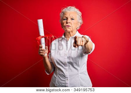 Senior beautiful student woman holding diploma standing over isolated red background pointing with finger to the camera and to you, hand sign, positive and confident gesture from the front