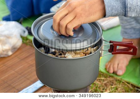 Camping Food Making. Pasta On Pan On Tourist Fire Stove. Camp Cooking A Mushroom Soup At The Lake Sh