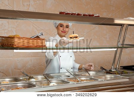 School Canteen Worker With Burger At Serving Line. Tasty Food
