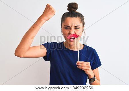 Young beautiful woman holding fanny party mustache over isolated white background annoyed and frustrated shouting with anger, crazy and yelling with raised hand, anger concept