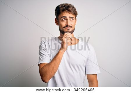 Young handsome man with beard wearing casual t-shirt standing over white background with hand on chin thinking about question, pensive expression. Smiling with thoughtful face. Doubt concept.
