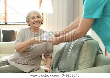 Medical Worker Taking Care Of Elderly Woman In Geriatric Hospice