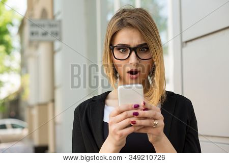 Woman Shocked With Sms Message On Phone. Closeup Woman Girl Looking At Cellphone Stunned Surprised F