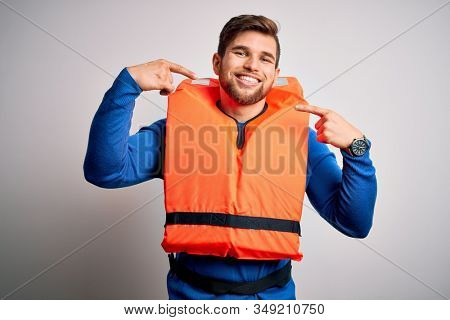 Young blond tourist man with beard and blue eyes wearing lifejacket over white background smiling cheerful showing and pointing with fingers teeth and mouth. Dental health concept.