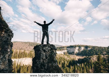 Young Man Standing With Raised Hands On Top Of A Mountain And Enjoying Valley View