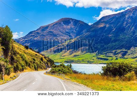 The road around the lake. Grassy mountains surround the Hawea Lake. South Island, New Zealand. Journey to the ends of the earth. The concept of ecological, active and phototourism
