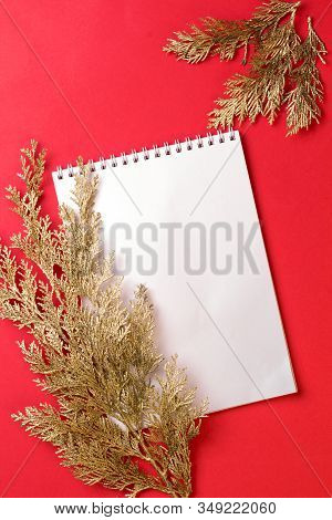 Golden Branch With A Card On A Red Background. Copy Space.