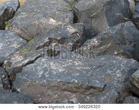 Basalt Black Rocks On Sea Shore With Sand And Salt Sediments, Close Up