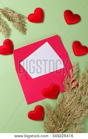 Golden Branch With Card And Hearts On A Green Background. Copy Space.