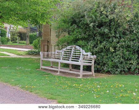 Empty Wooden Bench With Decorative Backrest On A Green Lawn Of A Park On Sunny Summer Day