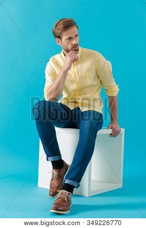Bothered casual man looking away and frowning, while holding his hand on his chin and sitting on blue studio background