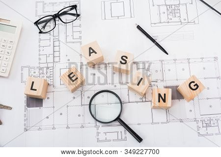 Top View Of Wooden Cubes With Leasing Lettering Near Glasses, Pen, Magnifier And Calculator On Bluep