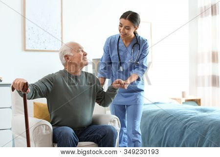 Care Worker Helping Elderly Man With Stick In Geriatric Hospice