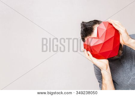 Young Woman Holding Polygonal Diamond Shaped Red Heart In Front Of His Head