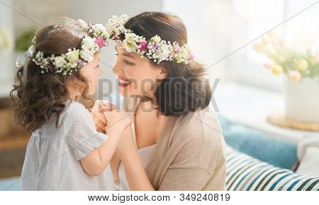 Happy mother's day! Child congratulating mom. Mum and daughter smiling and hugging. Family holiday and togetherness.