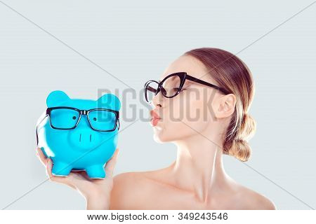 Glasses Sale Concept. Happy Woman Kissing Piggy Bank Wearing Eye Wear Glasses. Female Model Isolated