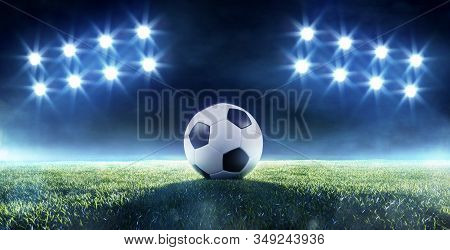 Soccer Ball On A Football Field Backlit By Two Banks Of Eight Bright Shining Spotlights In A Grass L