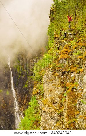 Travel, Holidays. Tourist Woman Standing On Cliff At Voringsfossen Waterfall. Mabodalen Canyon Norwa