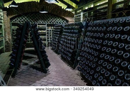 Wine cellar with wine bottles. Old wine bottles covered with dust and cobwebs are in the wine cellar of winery. Alcohol drink vintage storage