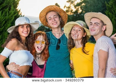 Group Of Beautiful Teenagers Hugging Each Other At Party.