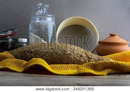 Oatmeal Diet Bread On A Yellow Towel In The Background Is Satiated For Flour, A Jar Of Flour, And A
