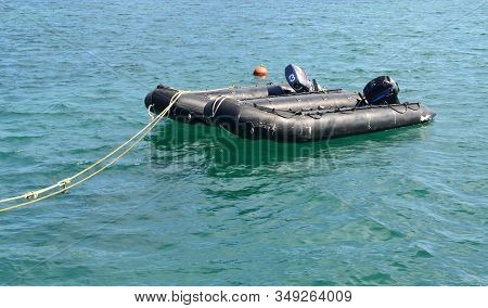 Two Black Rescue Boats Are Tied With Rope In The Sea